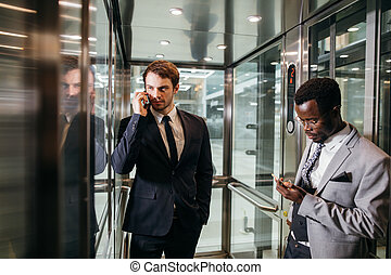 Business man standing in elevator and use smartphone