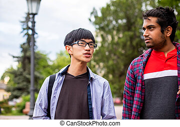 Two multiracial male best friends meeting outdoors