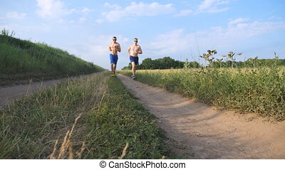 Two muscular men running and talking outdoors. Young athletic guys jogging over the field. Male sportsmans training together at nature. Friends exercising outside. Slow motion Healthy active lifestyle