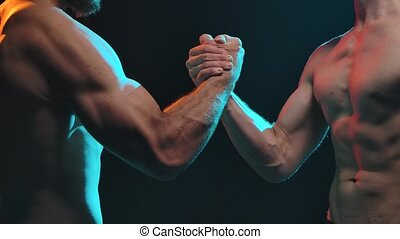 Two muscular, naked-chested men shake hands. Shot in the studio on a black background. Slow motion. Close up