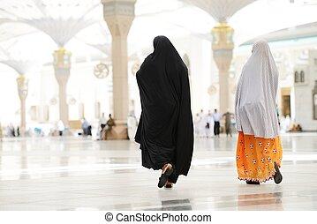 Two Muslim Arabic women walking - Islamic Holy Place