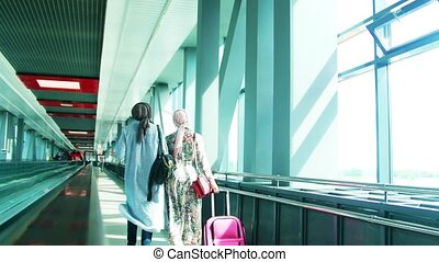 Two Muslim girls walking along the windows in the airport