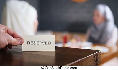 Two muslim woman sitting on the background and talking. A person puts the reserved sign on the table. Mid shot