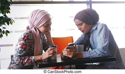 Two Muslim women drink coffee and communicate in the hand...