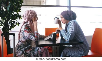 Two muslim women drink coffee and communicate - Two muslim...