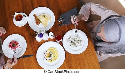 Two muslim women sitting in a restaurant. Plates with simple...