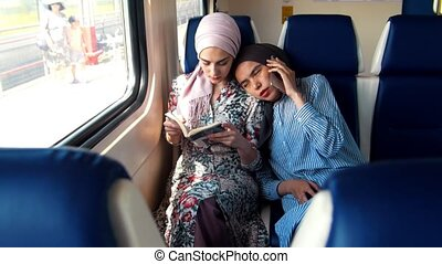 Two Muslim women traveling by train, one woman reads,...