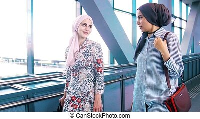 Two muslim women traveling in airport on escalator, at sunny...