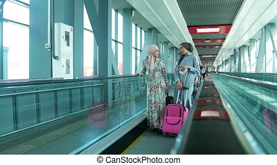 Two muslim women traveling in the railway station, at sunny...