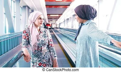 Two muslim women traveling in the stantion and communacation...