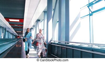 Two muslim women traveling in the station , at sunny day
