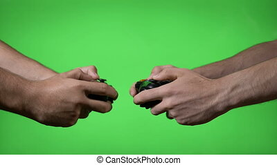 Two nervous young video gamers with wireless controllers facing each other in a match on green screen background