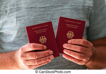Two new German passports in the hands of a man