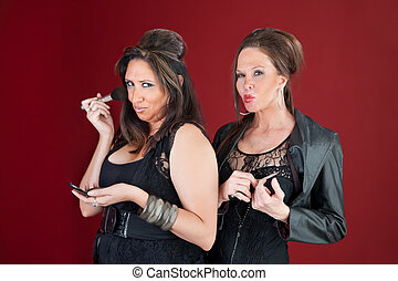 Two sexy middle-aged New Jersey style housewives dressed in black prepare their makeup