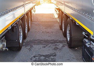 Two new truck semi-trailers are parked in a truck stop. ...