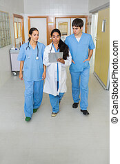 Two nurses and a doctor walking in a hallway