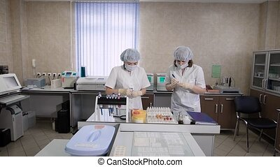 Two nurses in white coats check tubes with a blood test of patients to do the research under a microscope or put glass test tubes in a hospital centrifuge
