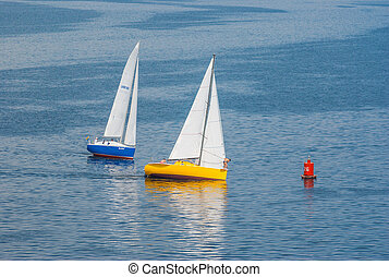 Two o yachts turning of the sailing race on the Dnepr river during city yacht club championship