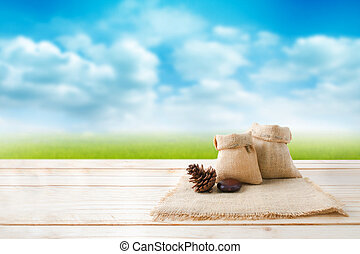 Two of blank hemp sack bag and pine cones on wood table top floor over blur green field and blue sky background with copy space