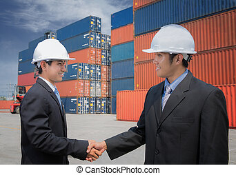 Two of Mid adult businessman shaking hands near cargo...