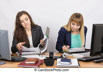 Two office employee sitting at a desk and working with papers and documents