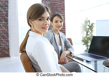 office workers sitting behind a Desk.