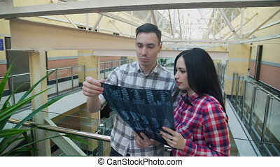 Two office workers stand in corridor and examine X ray image. Tall young man with dark hair standing, leaning on railing, holding in hands radiograph of spine and talking to employee about diagnosis of doctor, actively gesticulates, worrying about health. Beautiful brunette woman, in red checkered ...