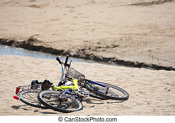 Two old bikes on the beach.