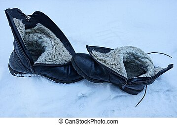 two old black leather boots in a white snowdrift