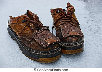 two old brown leather boots stand on white snow