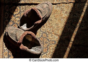 two old brown slippers on a rug in sunlight