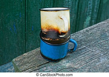 two old charred metal mugs on a gray wooden table