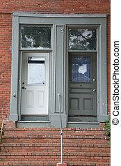 Two Old Doors in Brick Building