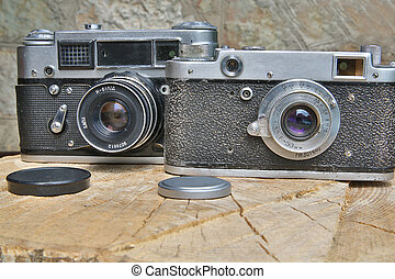 Two old fashioned cameras are in shape