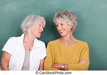 Two old friends enjoying a gossip standing side by side chatting and laughing in front of a green blackboard