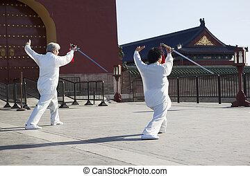 Two old men dancing swords in the park