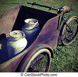 two old milk cans transported by an old wagon