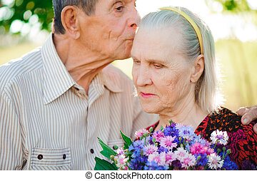 Two old people relax and hug each other in a park.