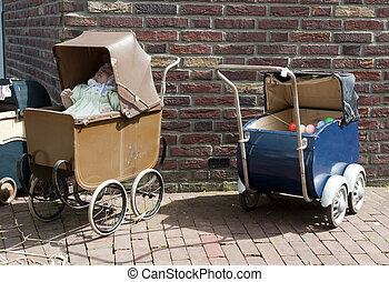 two old pram with a doll in it