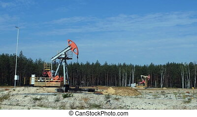 Two old Pump Jacks on an oil well in Russia, slowmotion