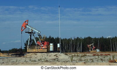 Two old Pumpjacks on an oil well in Russia, slowmo
