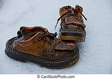 two old ragged brown boots on the snow