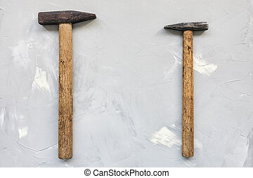 Two old rusty hammers on gray background