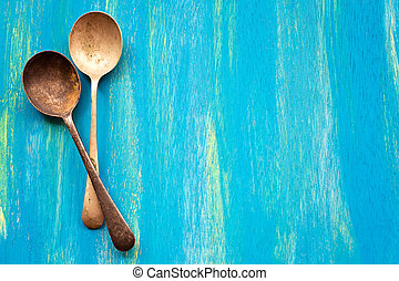 Two Old vintage spoons on blue wooden background, top view