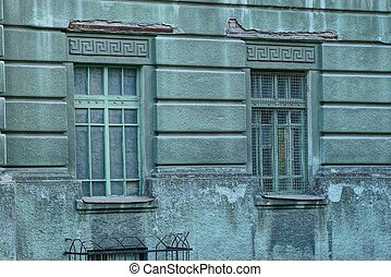two old windows on a gray green concrete wall