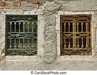 two old windows with decorative metal grid in Venice