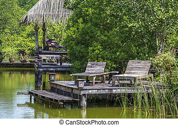 Two old wooden deck chairs near the lake water in a tropical garden, asia, Thailand