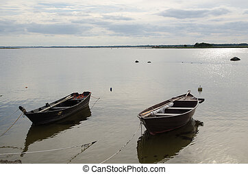 Two old wooden rowing boats by the coast