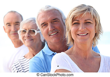 Two older couples standing in a line