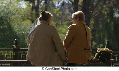 Two older women sitting on a bench talking together enjoying a sunny autumn day